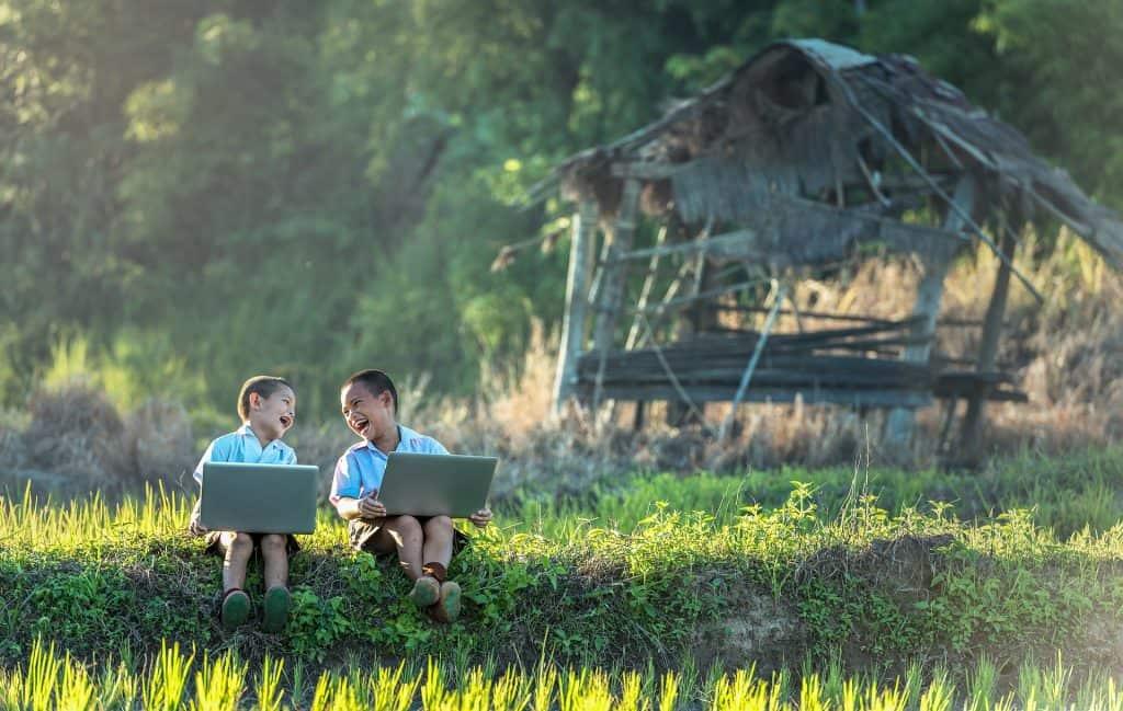 kinderen met laptop in de natuur